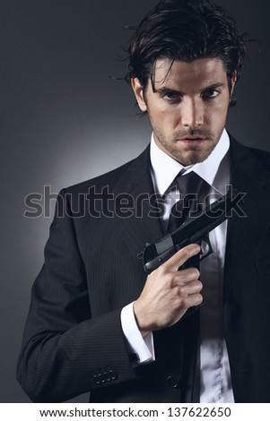Elegant and handsome spy posing with gun in hand. Grey backdrop portrait. - stock photo