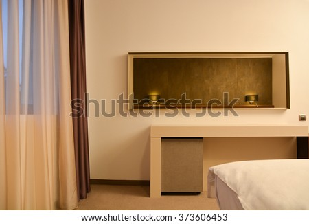 Elegant and modern desk in a hotel room, with a long mirror