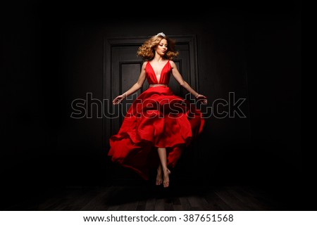 Elegant and passionate woman with tiara on her head in the red evening fluttering dress is capture in move, hovering above the ground, the wooden door is on the background - stock photo