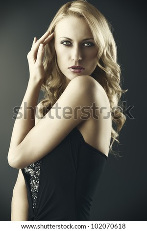 elegant and sexy woman in black with shorts and with a curly hair style over black background, she looks in to the lens with sensual expression, her left hand is near the right side of the head