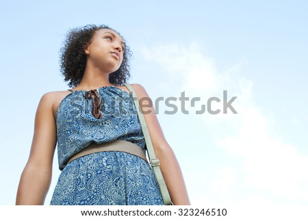 Elegant and stylish african american black teenager girl standing against a blue sky relaxing, looking away, being moody outdoors. Young bohemian woman lifestyle. Aspirational living, exterior. - stock photo