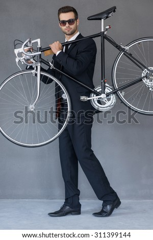 Elegant and stylish. Full length of confident young businessman carrying his bicycle on shoulder while standing against grey background - stock photo
