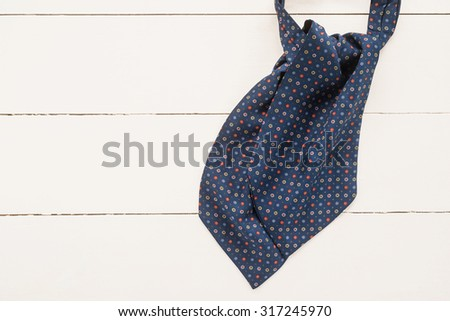 Elegant ascot tie on a wooden background   - stock photo
