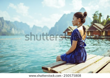 Elegant Asian girl sitting next to tranquil lake wearing a blue dress in Khao Sok National Park, Thailand - stock photo