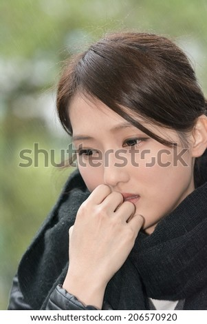 Elegant Asian woman of sadness in winter drizzling days. - stock photo