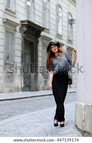 Elegant Asian woman with black hat on the street