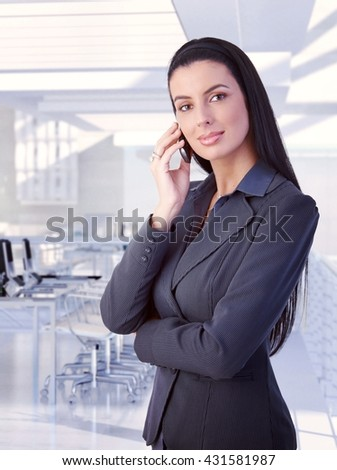 Elegant attractive brunette caucasian businesswoman with mobile phone standing at classy business office. Smiling, looking at camera, copyspace, suit.