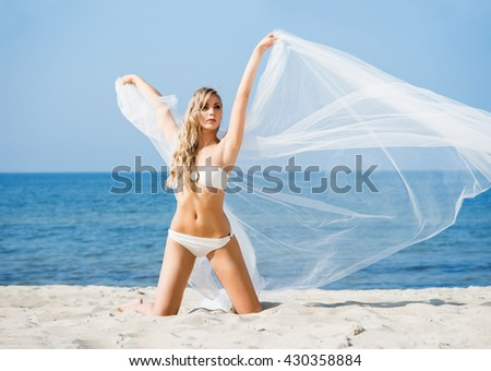 Elegant, attractive woman in alluring swimwear posing on the beach with blowing silk. - stock photo