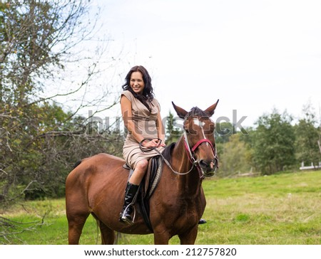 Elegant attractive woman riding a horse