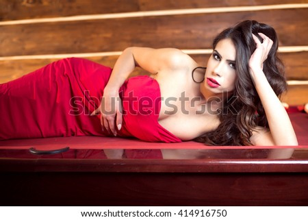Elegant attractive young adult woman lying down on pool table wearing solemn red ball dress - stock photo
