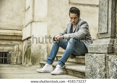 Elegant attractive young man outdoor wearing wool coat, in European city, looking at camera, sitting on marble steps