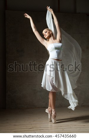 Elegant ballerina dancing in white costume and ballet shoes - stock photo