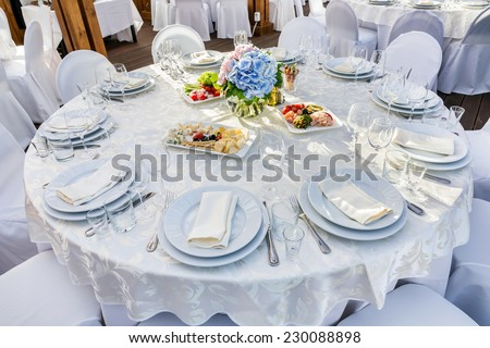 Elegant banquet tables prepared for a conference or a party and covered with a white tablecloth and decorated with flowers for guests - stock photo