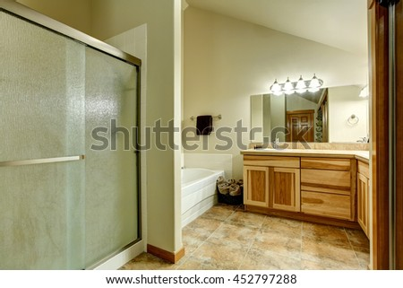 Elegant bathroom in soft tones with hardwood cabinets and marble tiled floor. White bathtub with tile trim in the corner and glass shower.