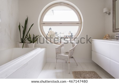 Elegant bathroom with bright tiles and a rattan chair beside a large round window overlooking the neighbourhood
