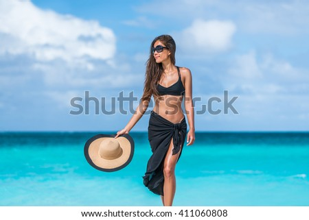 Elegant beach woman in bikini and fashion sarong standing on shore. Sexy lady in black beachwear, floppy hat, sunglasses enjoying sun on tropical destination during summer vacation in the Caribbean. - stock photo