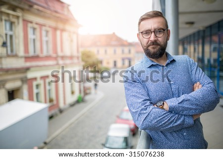 Elegant bearded fashion man standing at balcony with arms crossed and smiling - stock photo