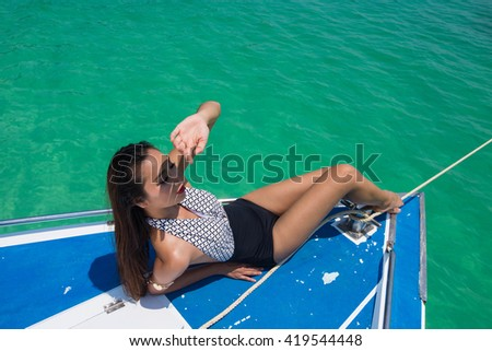 Elegant Beautiful Asia Thai Woman Girl Tan Skin in Black White Tan Skin on Paradise Deep Green Ocean, Island, Myanmar, lying on Yatch