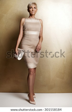 Elegant beautiful blonde woman posing in studio, wearing fashionable dress and bag. Lady with short hair.