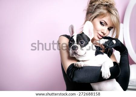 Elegant beautiful blonde woman posing witg pug dog over pink background. - stock photo