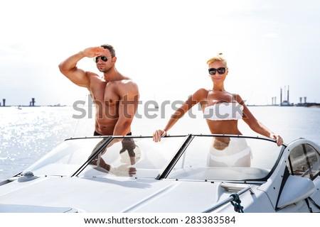 Elegant beautiful couple on a boat in a swim wear - stock photo