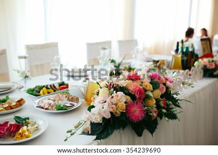 Elegant beautiful decorated table with meals and tableware at wedding reception closeup - stock photo