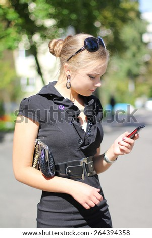 Elegant beautiful girl in a black dress with phone in hand - stock photo