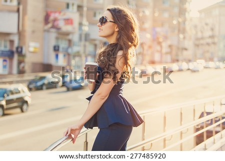 Elegant beautiful girl in the sunset outdoor on the street.