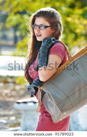 Elegant beautiful woman holding a bag in glasses