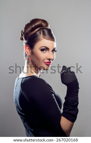 Elegant beautiful woman in a black cocktail dress and long gloves looking at camera - stock photo