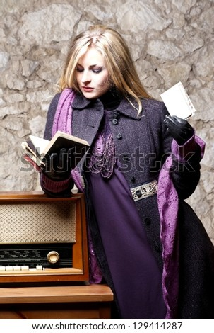 Elegant beautiful woman with book and vintage radio in country house