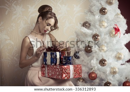elegant beautiful woman with hair-style sitting near decorated tree with some Christmas presents. Xmas concept.