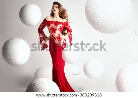 Elegant beautiful woman with long curly hair and glamour makeup posing in evening dress, looking at camera. Studio shot. - stock photo