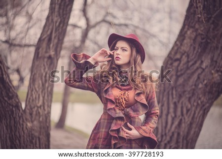 Elegant beautiful young woman in a vintage hat burgundy color and the old coat walks on cold autumn park, fashion, English style