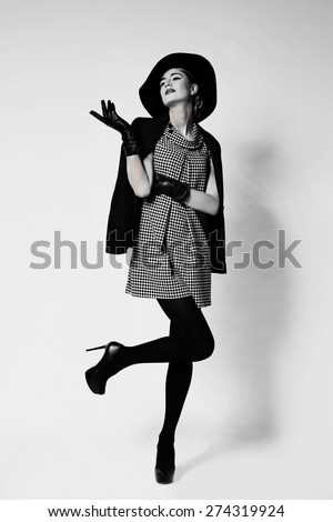 Elegant beautiful young woman in retro style dress, gloves, hat standing over light grey background - stock photo