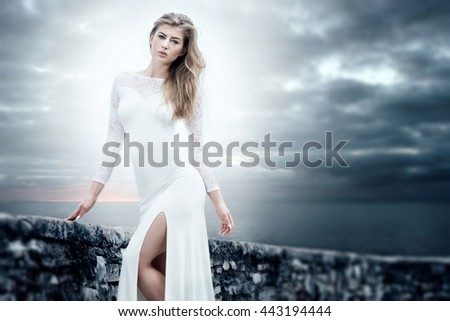 Elegant beautiful young woman posing in white dress. Sea on background.
