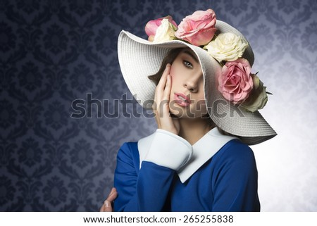 elegant beauty portrait of young lady with vintage hat with spring flowers as ornament looking in camera - stock photo