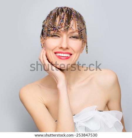 Elegant beauty woman. Fashion photo of beautiful woman with creative hairdo with bead strands over grey background. copy space - stock photo