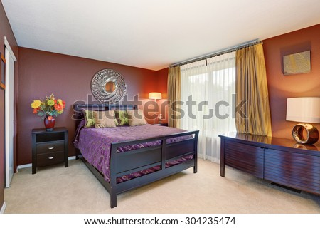 Elegant bedroom interior with purple and red decor tones. - stock photo