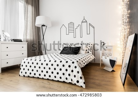 Elegant bedroom interior with white furniture and dotted sheets on bed
