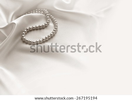 Elegant beige background with lace, silk and pearls - stock photo