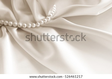 Elegant beige background with silk and pearls