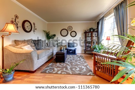 Elegant beige living room with blue and old  mall TV and hardwood floor. - stock photo