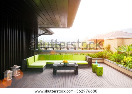 elegant bench and table on wooden floor outside house with sunbeam - stock photo