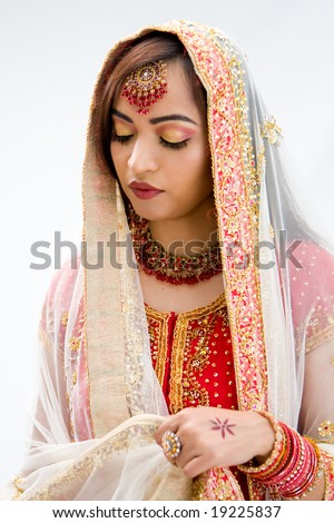 Elegant Bengali bride arranging veil looking down, isolated