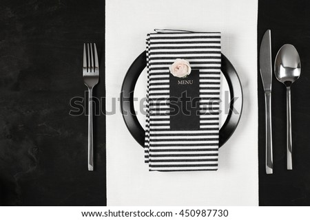 Elegant black and white table setting: plates on linen, striped napkin, blank label with rose and silverware. Top view point. - stock photo