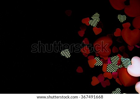 Elegant black background with red and various hearts. - stock photo