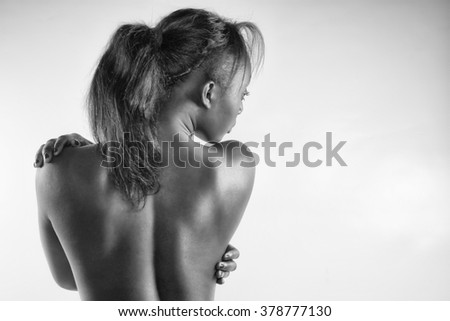 Elegant black woman from back on grey background in black and white