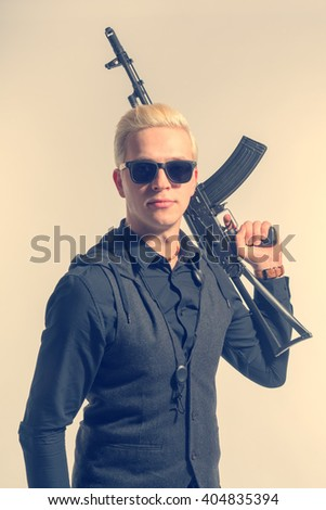 Elegant blond man in sunglasses dressed in black holding a assault rifle. Toned