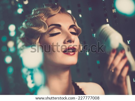 Elegant blond retro woman singer with beautiful hairdo - stock photo